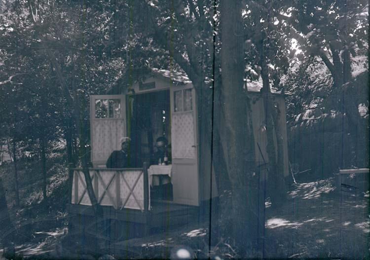 """G.L. Forslind och en annan man sitter i ett litet hus i en trädgård. """"G.L. Forslind vid Samskolan 1915 L.l."""""""
