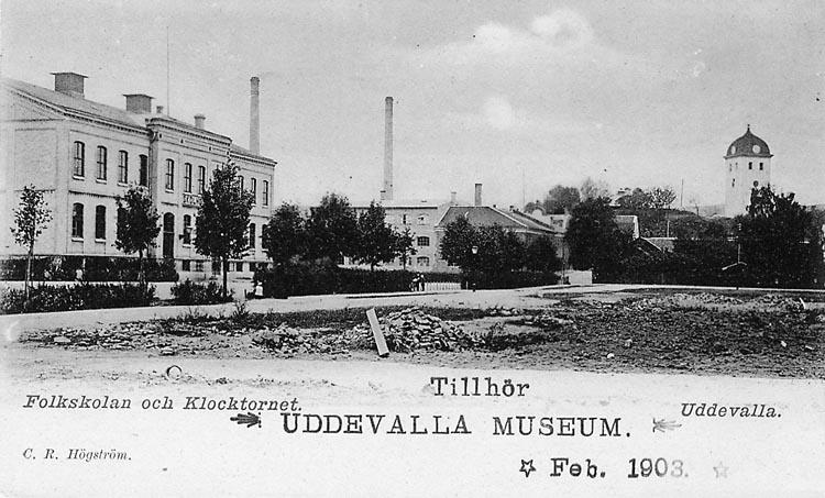 """Tryckt text på vykortets framsida: """"Folkskolan och Klocktornet. Uddevalla""""."""