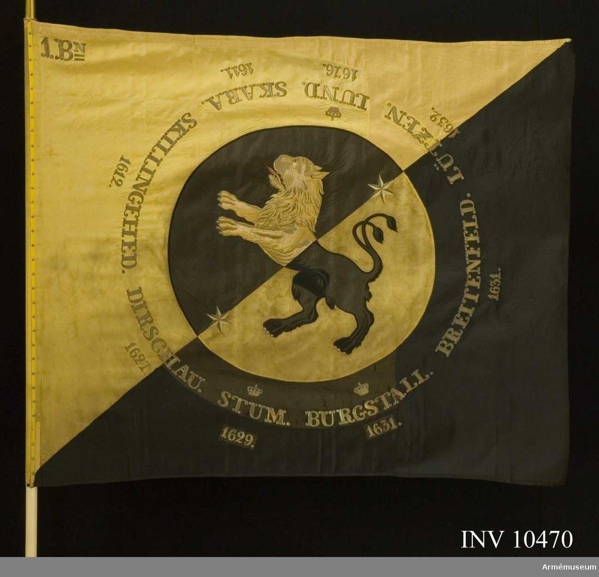 """Grupp B.  Duk av fansiden i fyrskaftad kypert, delad diagonalt i två fält - det inre gult och det yttra svart. I mitten en cirkel med 800 mm radie med omvända färger och där-  inne västergötlands sköldemärke: ett lejon, gult på det svarta  och svart på det gula fältet. I fältens delning finns två sex-uddiga stjärnor i guld. Lejonets svarta är applicerat fansiden  med kantsöm i svart silke, det gula är dels applicerat fansiden, dels schattérsöm i gult och vitt siden. Tungan fodrad i rött silke. Omkring vapnet, genombroderat i guld, finns segernamn: SKARA med """"1611"""" under, SKILLINGEHED med 1612, DIRSCHAU och1627,  krönt STUM och 1629, krönt BURGSTALL och 1631, BREITENFELD och  1631, LÜTZEN och 1632 samt krönt LUND med 1676. I övre inre hörnet finns """"1.Bn"""" broderat i guld (två streck  under N). Duken är kantad med ripsband, svart på det svarta och gult på  det gula. Fastspikad med förgyllda spikar.Kravatt av gult och svart kypertvävt fansiden. Guldfrans på  kortändarna.  Hel längd 2860 mm, frans 10 mm, bredd 260 mm. Kravatten fanns inte tillsammans med fanan i december 1968.Stång av furu - vitmålad. Doppsko konisk med rund knopp av för-  gylld mässing. Längd 2560 mm.Spets av förgylld mässing, ursprungligen med Oscar I:s krönta  monogram som senare felaktigt byttes mot Gustav V:s krönta spegelmonogram inom lyra av lager. Längd 330 mm.Fodral av mörkblått (svart) kläde med skinnskodd topp, dragsko och ficka för spetsblad. Längd 1820 mm, bredd 180 mm.  Samhörande fana, kravatt, fodral."""