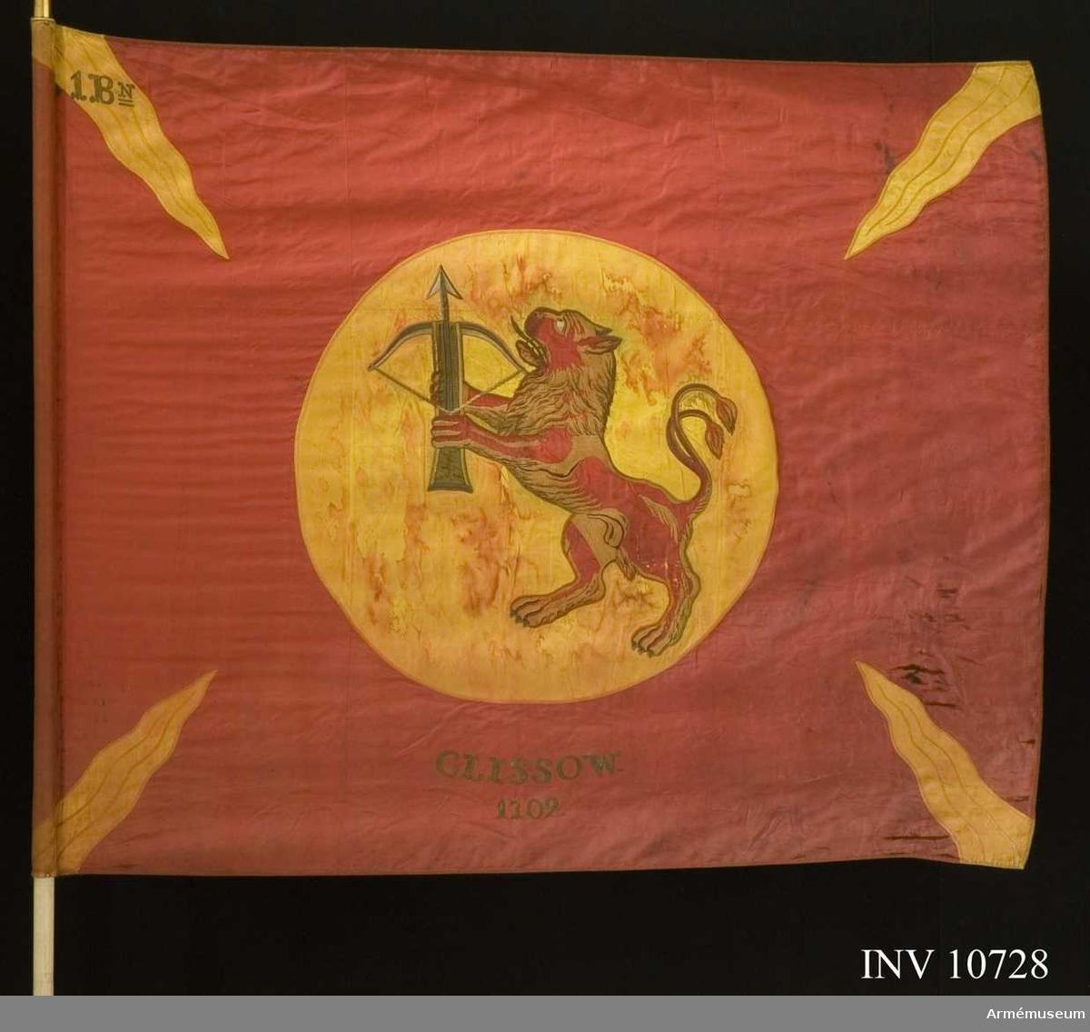 Grupp B.  Duk av rött, fyrskaftat fansiden (kypert), med från hörn och sidornas mitt ingående 4 st flammor av gult liknande siden. I mitten, broderat lika påbåda sidor, Smålands vapen, i gult fält (830 mm) ett rött lejon förande ett spänt armborst med pålagd  pil. Lejonet av rött fansiden med man och skuggning i bruna  och violetta silken, tänder och klor i silver. Armborstens  stock brunt siden, silvertyg i bågen och och pilen, kantsömmar i plattsöm i olika silken. Segernamn under vapnet, genombroderat i guld: Clissow 1702. Kantad med sidenband och fäst med förgyllda spikar. Kravatt: blå och gul av fansiden, med pil och frans. Längd 1920 mm, bredd 290 mm. Stången av furu, målad vit. Doppsko av förgylld mässing. Spetsen av förgylld mässing. Ett fodral tillhör också. Fodralet i svart kläde med skinnskodd spets, dragsko och ficka för spetsens blad. Längd 1840 mm, bredd 180  mm.