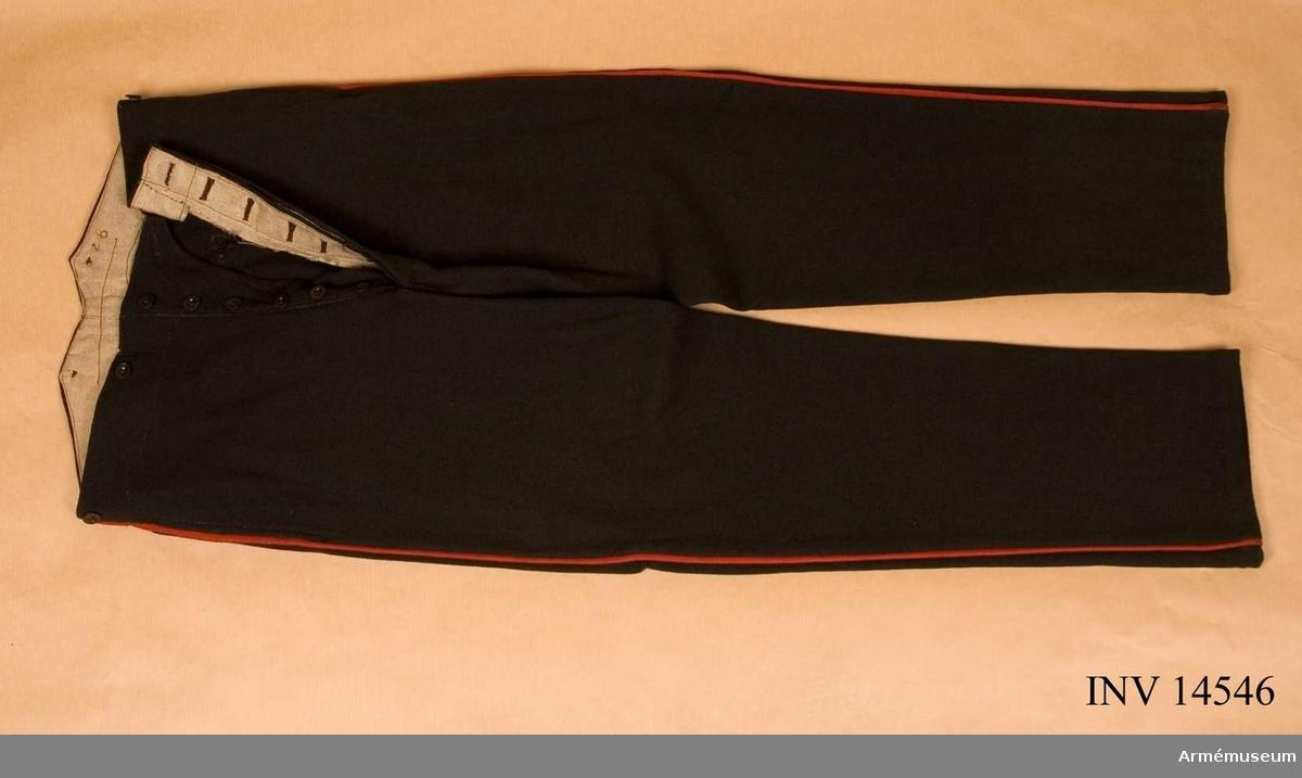 """Grupp C I. Byxor av svart-blått kläde, med två sidofickor. På byxornas yttre söm finns en röd bred passepoil. Knapparna äro 6 st för sprundet och 6 st för hängslen. Knapparna äro av svart metall. Foder av grovt linne på vilket det står """"28"""". På byxornas baksida finns fastklistrat en pappersbit på vilken det står: """"Heigt 5 ft. 10, Waist 34, Leg 33, C & J Webb & Co 17 Coleman ST. Litteratur: Die Englische Armée, Verlag von M. Ruhl sid 20, Infanteri Uniform. Byxorna av svartblått kläde med röd passepoil. Handbuch der Uniformkunde, Prof. Rich. Knötel, Hamburg 1937 sid 196. Infanteriuniform. År 1844 infördes av svart kläde byxor med röd passepoil."""