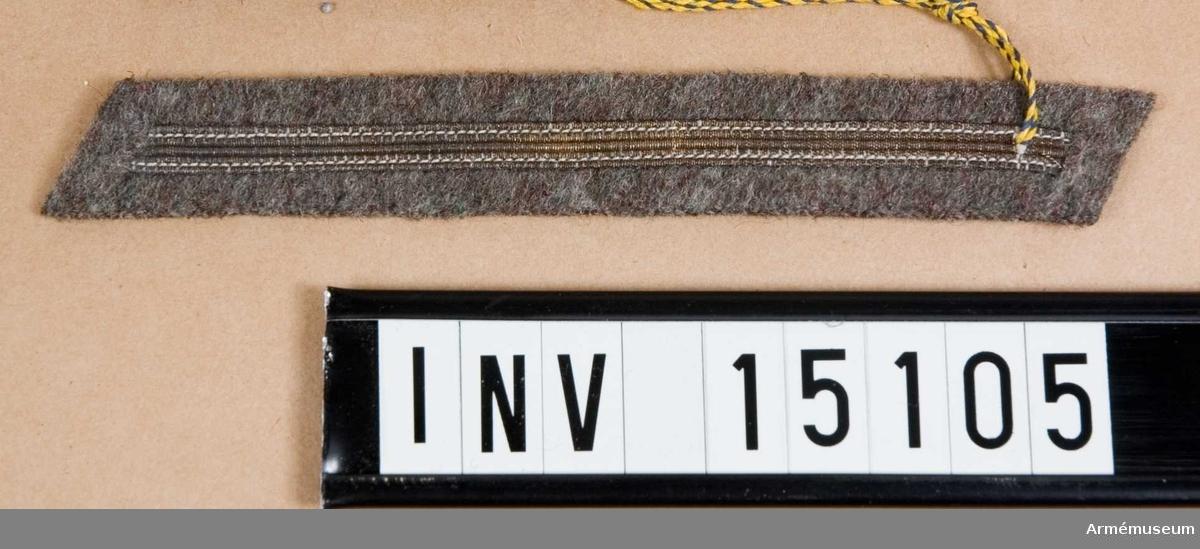 Grupp C I.  Från Kungl. Arméförvaltningens Intendenturdep, modellkammaren. Modell å examenstecken m/1925 för manskap vid alla truppslag, som genomgått korpralsutbildning (en silvergalon). Fastställd genom go nr 922/1925 den 1 juli.