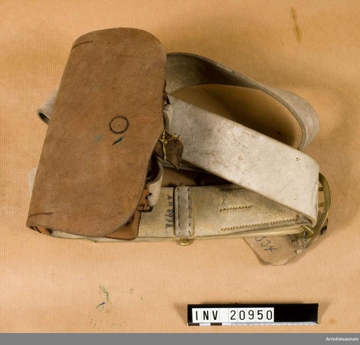 """Grupp C II. För dragoner, husarer, ulaner och reservkavalleri, Tyskland. Patronväska av brunt läder. Lock med en liten bit läder med  knapphål för stängning. Locket har text """"Loh, Berlin"""". Väskan som inuti har 20 fästen för patroner (karbin m/1871) infördes i tyska armén efter en dagorder av den 25 maj 1875. På väskan undersida två spännen för att fästa bandolär till väskan och en knapp av mässing för att stängning. På baksidan en läderbit med knapphål för sammankoppling med vapenrock. Rem av vit älghud med ovala spännen och beslag av 5 cm bred mässing. På ändarna två smala remmar för att koppla remmen vid  väskan. LITT  Das Deutsche Reichscheer. G Krickel, Berlin. Sida 83, 99. Patronväska infördes efter dagorder 27 maj 1875, för patroner till karbin m/71 - för dragoner, husarer och ulaner - år 1836.  I indenturen färgades icke patronväskorna som denna, i brun läderfärg, endast när de kom till regementena färgades och lackerades de i svart. Patronväskan har en kartongetikett med text """"Kartusche mit Bandoljer für Dragonen, Husaren und Reserven-Kavallerien. Berlin 1876. Militair-oneconomin Departament Abteilung für die Bekleidungs Angelegenheiten"""". Underskrift. """"ad Nr 104/1 MOD3"""". Enl Granberg."""
