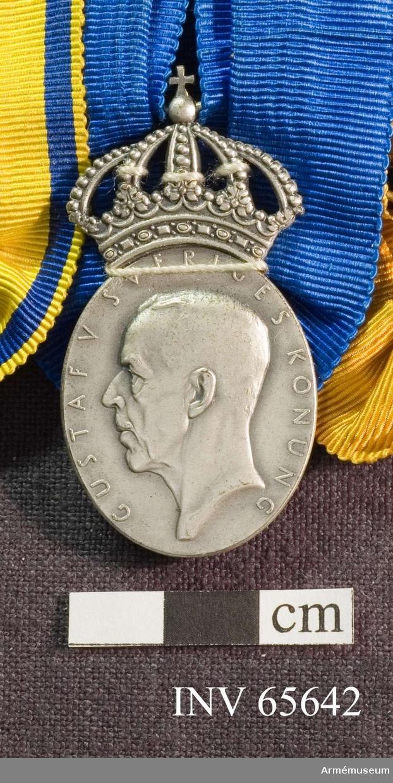 """Grupp M II. Medaljen är en oval med en kunglig krona ovanför. Åtsidan har kung Gustav V i profil samt """"GUSTAV V SVERIGES KONUNG"""" utmed kanten. Frånsidan har tre öppna kronor - två över en - bevingad granat samt """"RIKSLUFTSKYDDSFÖRBUNDET"""" utmed kanten. Under granaten en rektangel med """"T. GUSSING 1942"""". Under den en namnstämpel """"S & Co"""" (tillverkare) och fyra kontrollstämplar. Medaljbandet är blått och rynkat på ena långsidans mitt och hopdraget på att bandet har blivit U-format. På baksidan ett likadant behandlat band, fast dubbelvikt på längden."""