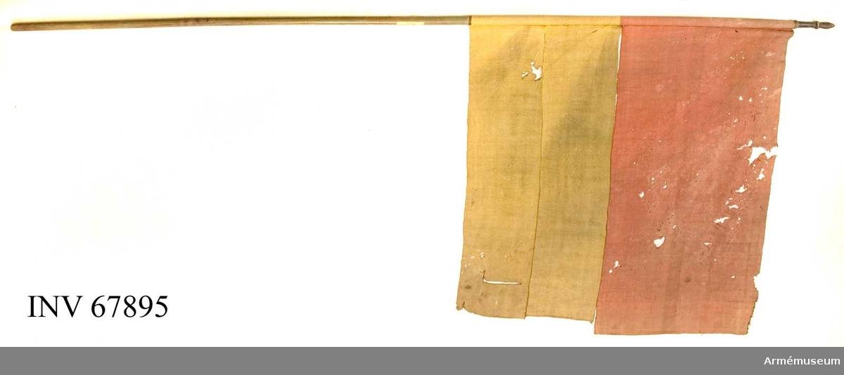 Duk: Tillverkad av enkelt gult och rött ylle. Sydd av tre våder. Övre delen röd. Kypertvävd av enkel kvalitet.  Duken fäst vid stången med järnspik, ursprungligen på en läderremsa.  Stång av grönmålat trä. Spets av svartmålat trä, översta delen lansettformad.  Märkning: Etikett kvar på stången troligen från Riddarholmskyrkan? Nr 77.