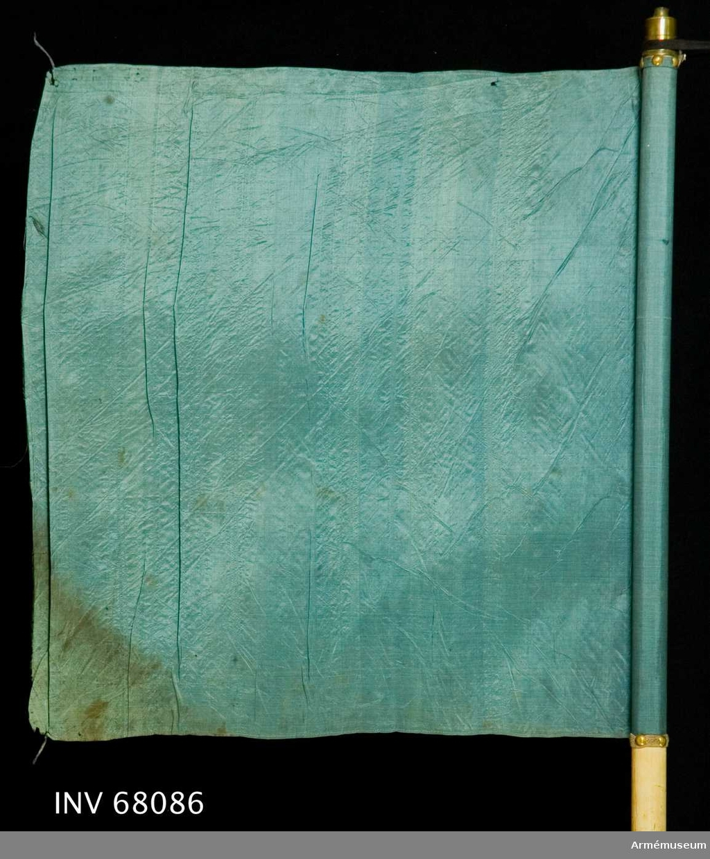 Duk: Tillverkad av enkel, blå sidentaft. Duken fäst vid stången med en rad tennlikor på ett gråblått band, 10 mm brett.  Dekor: Saknas.  Stång: Tillverkad av trä, vitmålad, smal.  Skinnremmar: En övre, vit skinnrem fäst vid stången på 685-700 mm längd från dukens nedre fäste mätt, bildar en 315 mm lång ögla.  En nedre, brun skinrem fäst vid stången på 45-65 mm längd från stångens nedre ände mätt, bildar en 255 mm lång ögla.