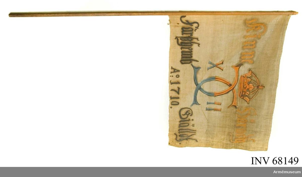 Duk: Tillverkad av enkel vit linnelärft, sydd av två horisontella våder. Fäst vid stången med en rad järnnagel.  Dekor: Målad på dukens insida i mitten, Karl XII:s namnchiffer, dubbelt med X - II på ömse sidor, krönt med sluten krona, i gult och brunt på den övre våden, blått och svart på den nedre. Text på ömse sidor om chiffret upptill i gult och nedtill i svart.  Stång: Åttkantig stång tillverkad av furu.