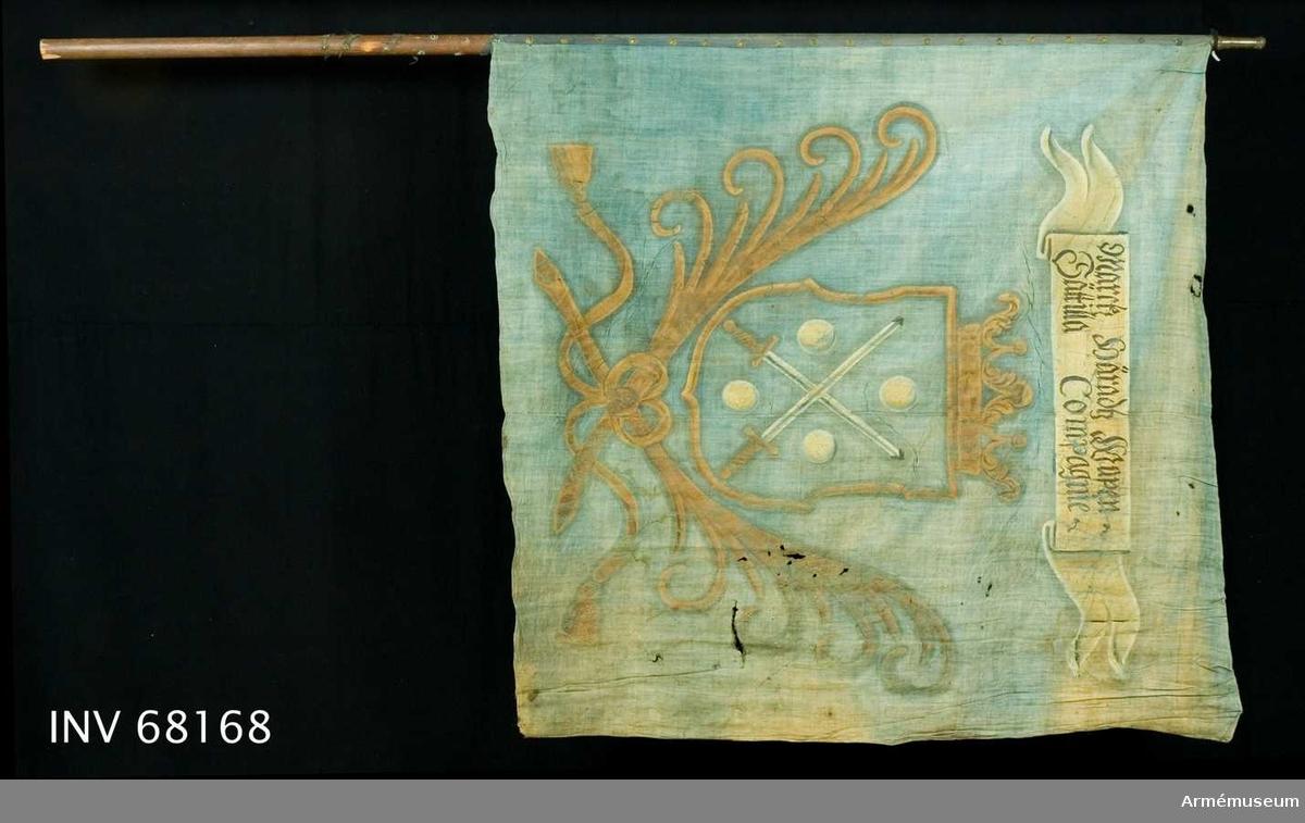Duk: Tillverkad av enkel blå linnelärft. två vertikala våder sammansydda med en smal fällsöm. Stad i vertikala ytterkanten. Fållen i över och underkanten lagd åt dukens utsida. Fäst med en rad sexuddiga tennlickor på ett blått band. Bandet har ursprungligen fortsatt 330 mm ned på stången.   Dekor: Målad lika på båda sidor. I mitten i gult en med öppen krona krönt sköld. Nedtill innefattad av två korsade svärd med vita klingor och gula fästen, följda av fyra i vinklar ställda vita kulor. På det vita inskriptionsbandet text i svart på båda sidor av duken.  Stång: Tillverkad av trä, avsågad, brunmålad. Holk av mässing.