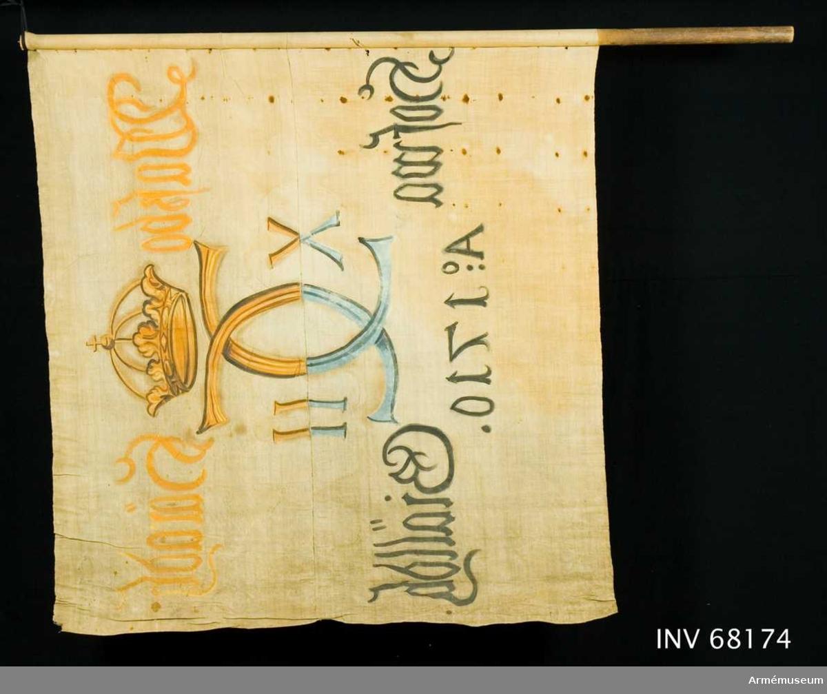 Duk: Tillverkad av enkel vit linnelärft. Sammankastad av två horisontella våder. Vertikala fållen lagd åt dukens utsida. Fäst med relativt små järnnagel på en något murken läderremsa.  Dekor: Målad endast på dukens insida (namnchiffret ifyllt även på dukens utsida), i mitten Carl XII:s namnchiffer, krönt med sluten krona, dubbelt C, på ömse sidor om detta X-II i gult och brunt på övre våden på den nedre i svart och blått.  Text på ömse sidor om chiffret, upptill i gul och nedtill i svart. Under chiffret text i svart.  Stång: Målad mörkbrun. Avsågad upptill och nedtill. Skruv uppstickande i stångens övre ände.