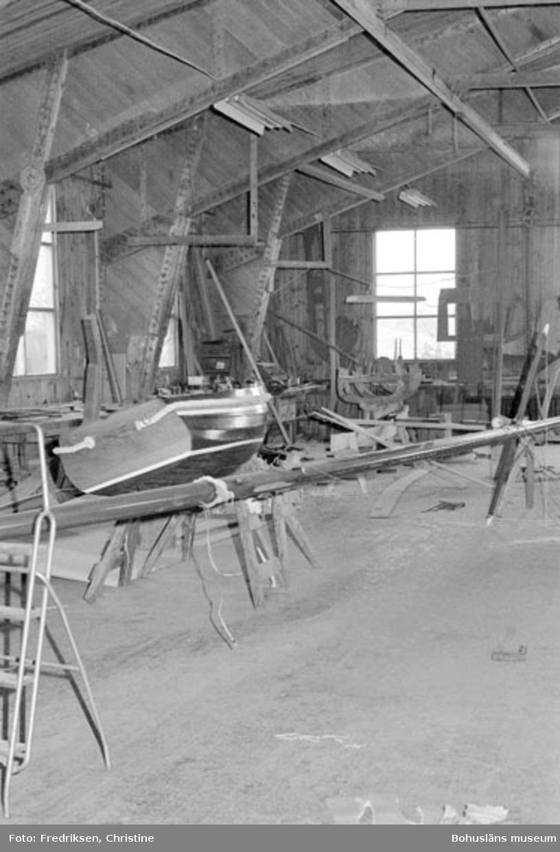 """Motivbeskrivning: """"Allmags varv, Allmag, Orust. Interiör från båtbyggarverkstaden. På bilden syns en färdig dinge och till höger därom, längre bort i bilden, en dinge under byggnation (resning och uppsatta mallar)."""" Datum: 19800710 Riktning: Nö"""