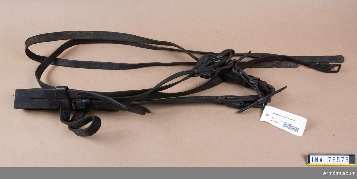 Grupp: K: I.  Betsel utgöres av: 1/ huvudlag, 2/ tränsbett och 3/ tyglar.  1/ Huvudlaget består av: a/ nackstycke, 40 mm brett, med dubbla stroppar. b/ sidstycken, 20 mm breda, varje med två söljor. c/ käkrem, 20 mm bred, med en sölja. d/ pannrem, 22 mm bred, rörlig.  2/ Tränsbettet är dubbelt. Varje tränsbett har tvådelat bett med 12 cm bredd mellan tygelringarna och består aven kortare och en längre del. Den längre delen är förenad med en vanlig tygelring, 38 mm i diam, den kortaste delen är förenad med en tygelring som utgör även 11,5 cm:s lång parerstång.  3/Tyglarna äro 20 mm breda, hopspända vid tygelringarna. Ej hopsydda.