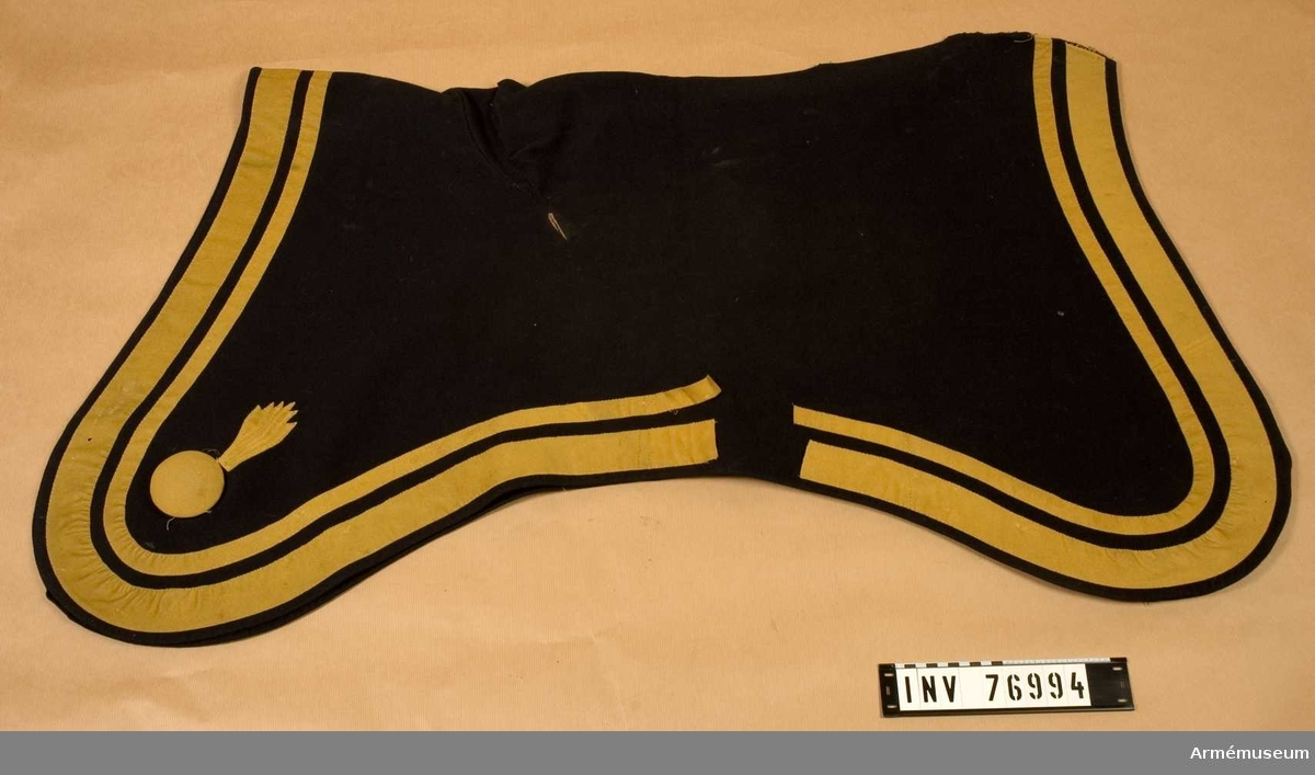 Grupp: K I. Regemente: Artilleriet.  Tillverkad av: mörkblått kläde med en smal och en bredare list av gult kläde.