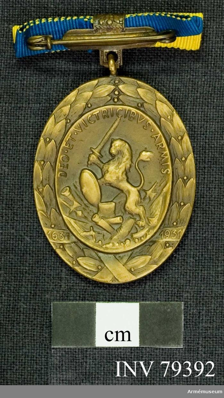 Grupp M.  Åtsidan: Konungens bröstbild, vänd åt höger i harnesk och mantelveck uppdragna över axlarne huvudet lagerkransat, infattat i en konkav medaljong. Omskrift: GVST.ADOLP.D.G. SVEC. GOT.WAND. REX. M.P.D.E.ET.GI.DO. Utanför medaljongen en densamma omslutande lagerkrans, ombunden på 4 ställen med band. På 2 av dessa står: 1631, 1931.   Frånsidan: Lagerkrans ungefär lika med åtsidans. Innaför: en medaljong varå synes ett på bakbenen stående åt vänster vänt lejon, hållande i högra framtassen ett svärd och i den vänstra en rund, kupig sköld. Lejonet går på en anselig grupp av krigsemblem såsom kanon, kanonkulor, fana, hillebarder, svärd m.m, omskrift: DEO . ET . VICTRICIBVS . ARMIS.   Medaljens översta ända slutar i en ögla, genom vilken är trädd en bandhållare.  Bandet är av rips, hälften blått och hälften gult på tvären. Beskrivning: Jämför Hildebrand, Gustaf II Adolf n:95. kmpl. C.P.