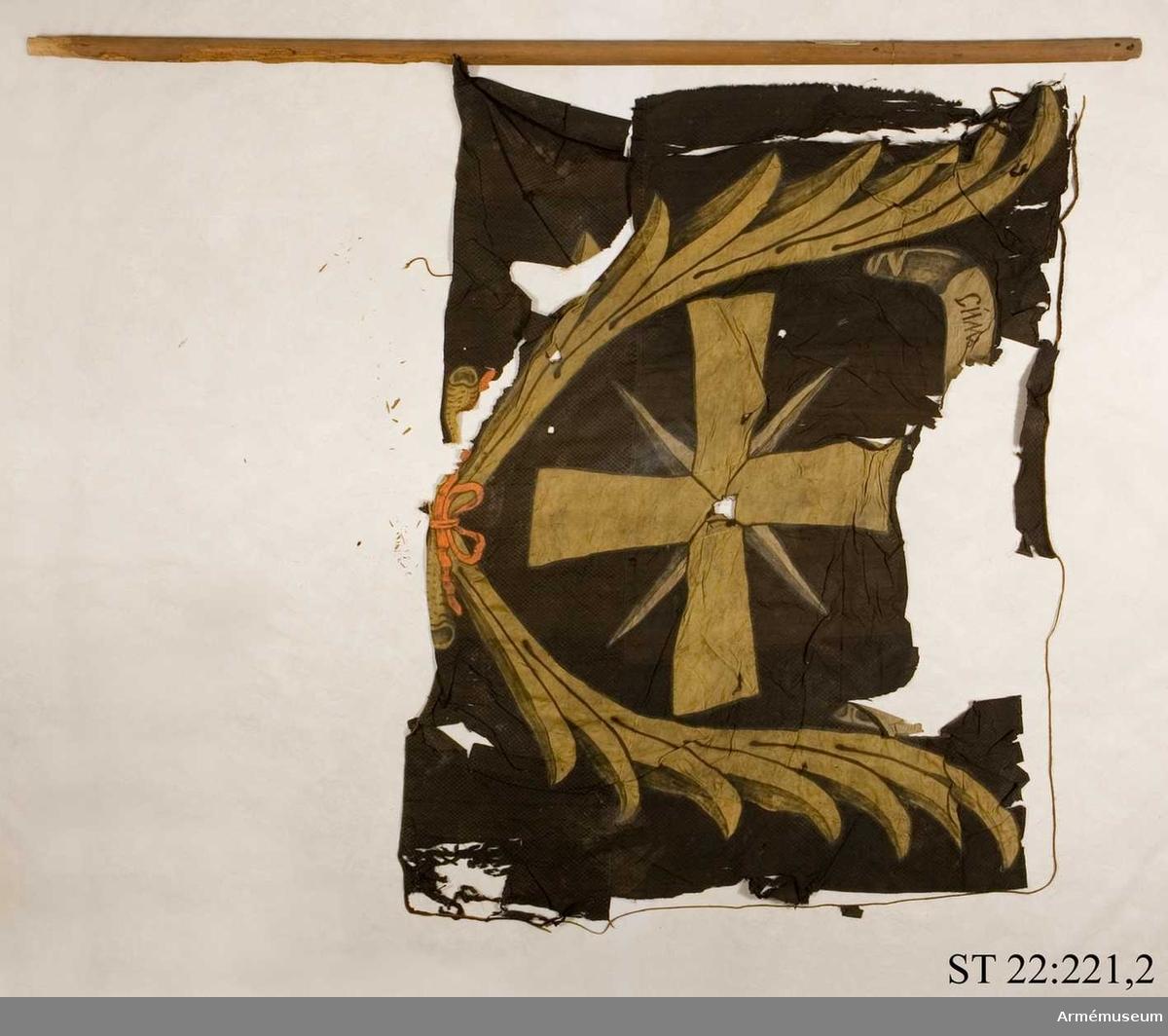 """Duk av svart sidendräll med infälld och målad dekor bestående av ett ursprungligen gult kors omgärdat av gula palmblad. I ett textband rysk text betydande: """"I detta tecken ska du segra"""". Duken saknar strumpa och är fäst vid en sekundär stång."""