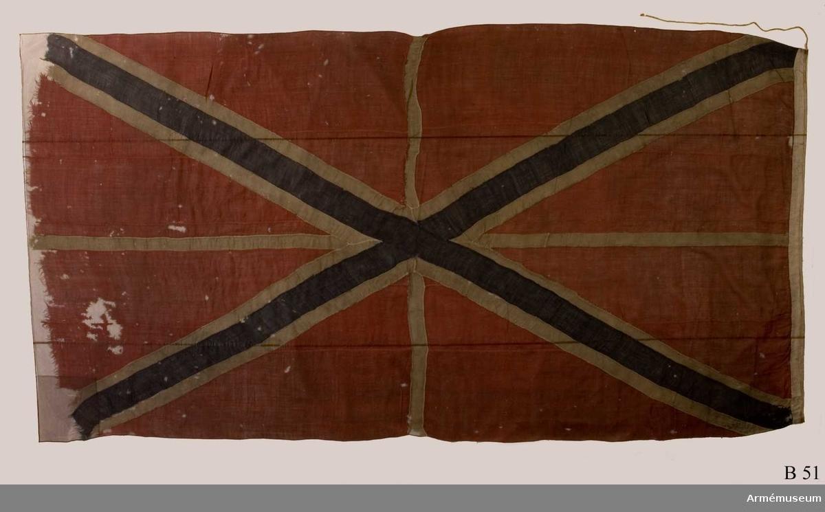 """Röd flagga med vitt kors samt ett blått andreaskors. Lik av vitt linne. På flaggan var tidigare fastsydd en etikett av pergament med texten: """"Denna ryska gös, 4 duk, är tagen uti bataillen vid Svenskund under Hans Kungl Majts egit höga befäl och anförande den 9 julij år 1790. No 3"""". Etiketten är borttagen vid konservering och förvaras nu i Trofésamlingens arkiv."""