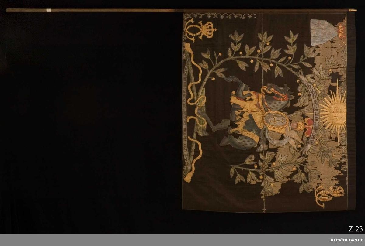 """Fana för Västmanlands kompani, Upplands tre- och femmänningsregemente.  Enkel duk av grön (nu brungul) taft med målad dekor. På ena sidan ärkeängeln Mikael ridande på häst, bärande ett svärd samt en sköld med IHS-inskription. Motivet omges av en lagerkrans hopbunden av guldrosett. Ovan kransen och St Mikaels huvud en triangel med Jahve-tecknet inom en strålsol. I övre hörnet mot stångsidan Västmanlands vapen, ett eldsprutande berg. I nedre hörnet mot stångsidan och flygsidans övre hörn Karl XIIs monogram. Kantbård av dekorativt vågband med blad. Dessutom ingår två språkband med texterna: """"Han begiärer mig, ty will iag uthiälpa honom"""" samt """"Lofwad ware Gud then min bön icke förkaster eller wender sin godhet ifrån mig."""". På andra sidan en krigare till häst, iförd rustning och hjälm samt svärd av lagerblad. I övrigt överensstämmer motivet med beskrivningen ovan. De två språkbanden har följande texter: """"Upp Herre och hielp mig min Gudh"""" samt """"Ty iag förlåter mig icke på min boga, ock mitt swärd kan ey hielpa mig, utan Du hielper oss ifrån wåra fiender."""". Målningen är utförd i färgerna rött, gult, grönt, brunt, blått, grått, vitt, svart, silver och guld. Fanan målad 1710-1714 troligen av Wickman. Trästång (3-4 cm i diam) med profillerad mässingsknopp. Beskrivning: EHC 1967  Kommentar: Ryttaren är klädd i en karusellrustning """"á la Romaine"""" av den typ som bland annat användes vid Karl XIs kröning. KTS 2010-08-30"""