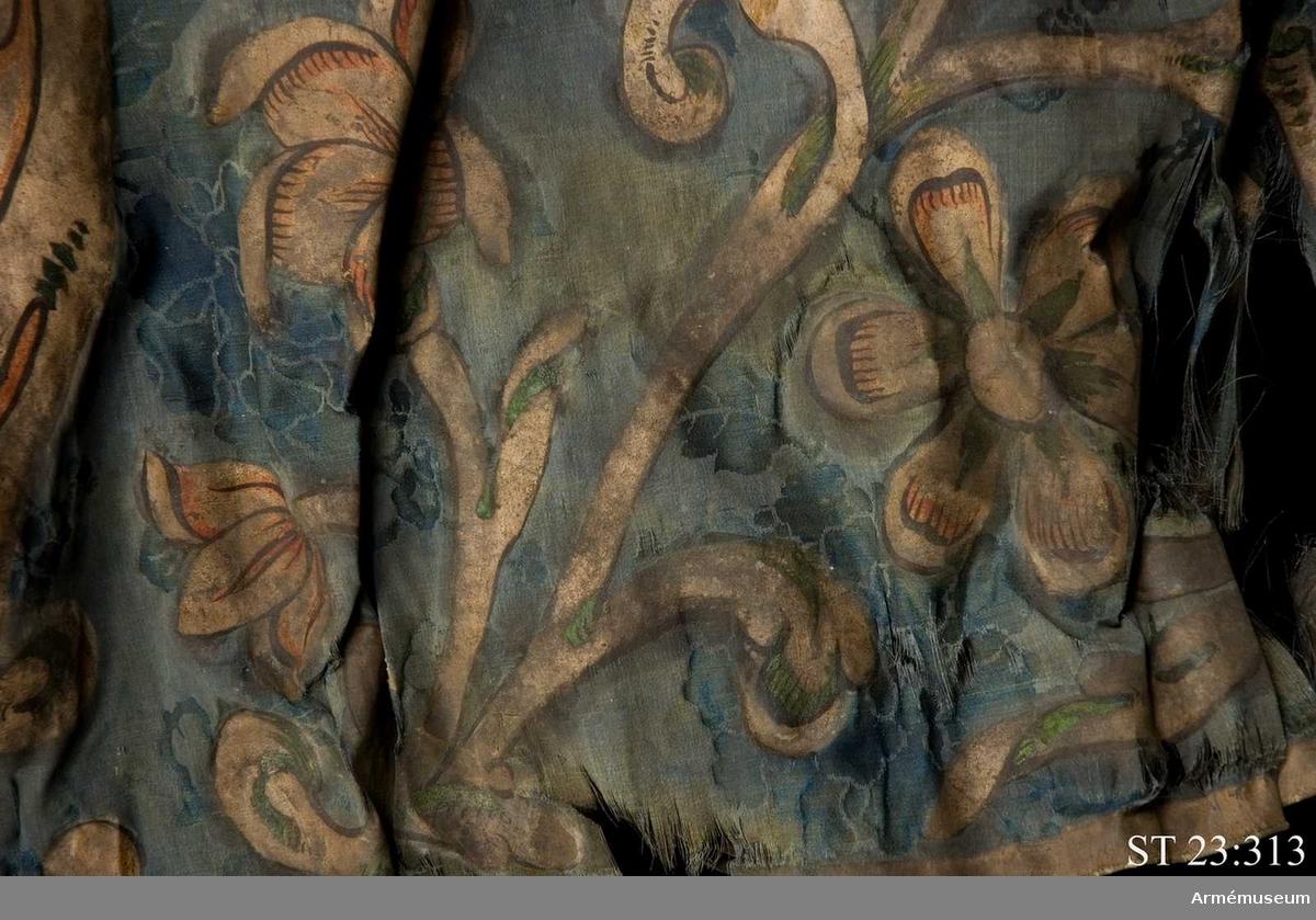 S:t Nikolaj i helfigur en face med svärd i stångsidehanden och ortodoxt kors i flygsidehanden, omgiven av oval kartusch, en böljande akantusranka med olika blommor, två cirkelrunda skivor, den ena mellan kartisch och grenverk, den andra på yttersya tungspetsen. Kantbård längs de fria sidorna.