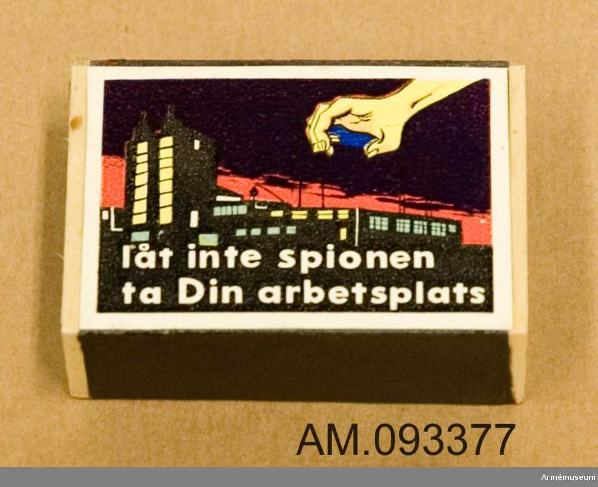 Tändsticksask med tändstickor. På ena sidan motivet Solstickan och på andra sidan ett motiv som illustrerar hur en spionhand sträcker sig över en husbyggnad nattetid.