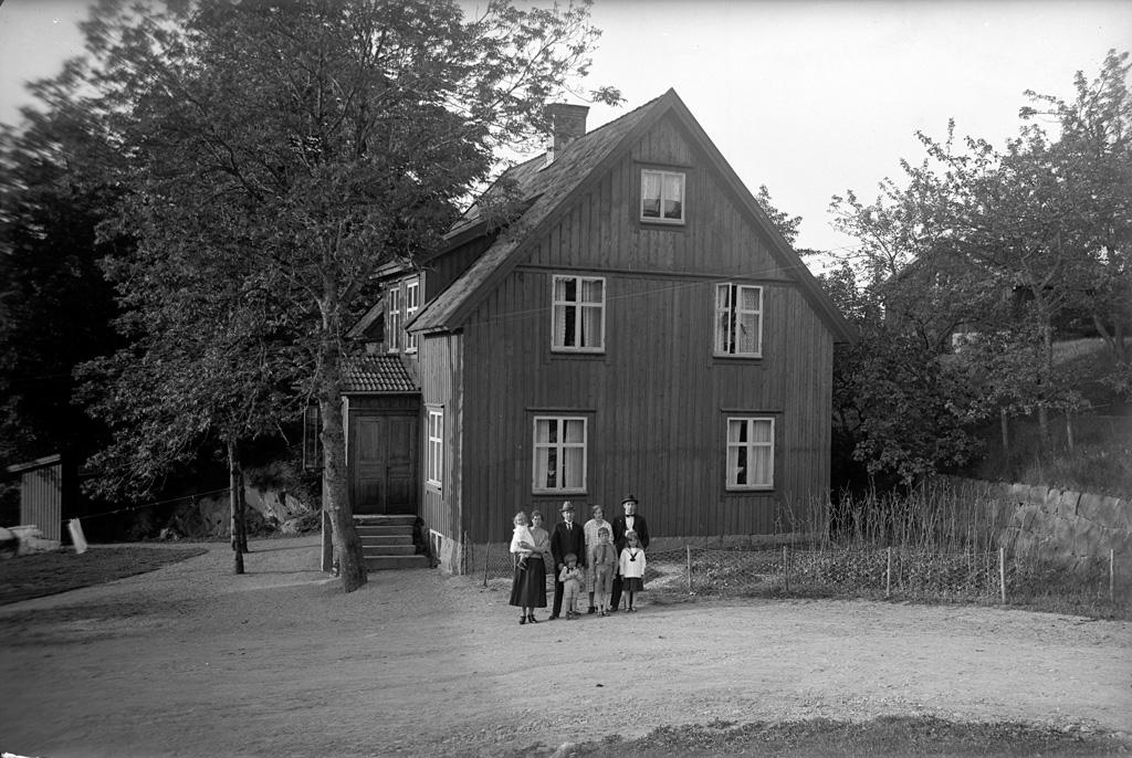 """Text till bilden: """"Hus m. persongrupp vid Fossums kvarn i det fria vid Karlsberg. Den 2/7 1923""""."""
