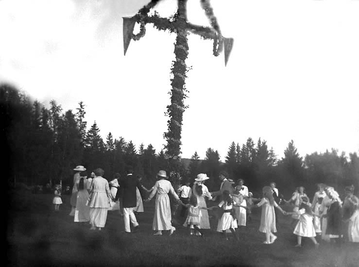 Män, kvinnor och barn dansar runt en midsommarstång