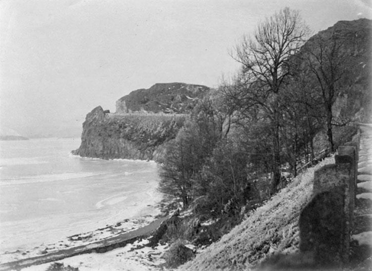 """Bilden var uppklistrad på ett A4 papper. På papperet under bilden stod följande handskrivna text: """"Uddevalla. Bodeleviken och nya landsvägen vid Hästepallarna""""."""
