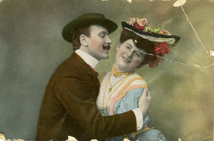Kolorerat postkort föreställande en man som håller om en kvinna, mannen försöker kyssa kvinnan som tittar mot betraktaren