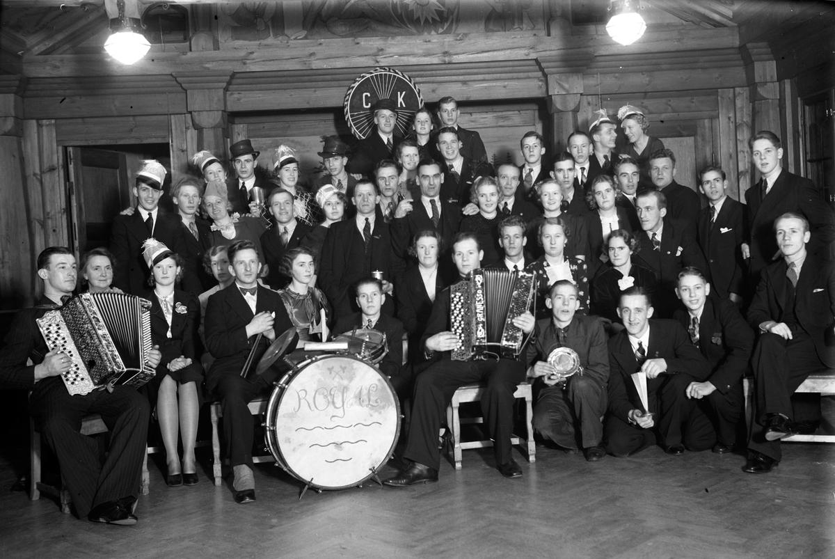 Gruppbild av Cykelklubben Revansche, år 1936. På väggen bakom dem hänger deras emblem, CKR. Sittande i första raden: nr 3 från höger är Einar Andersson. Stående i andra raden: Ordförande Nestor Lund (8). Två män har dragspel i knät och en sitter vid trummor med texten ROYAL på.