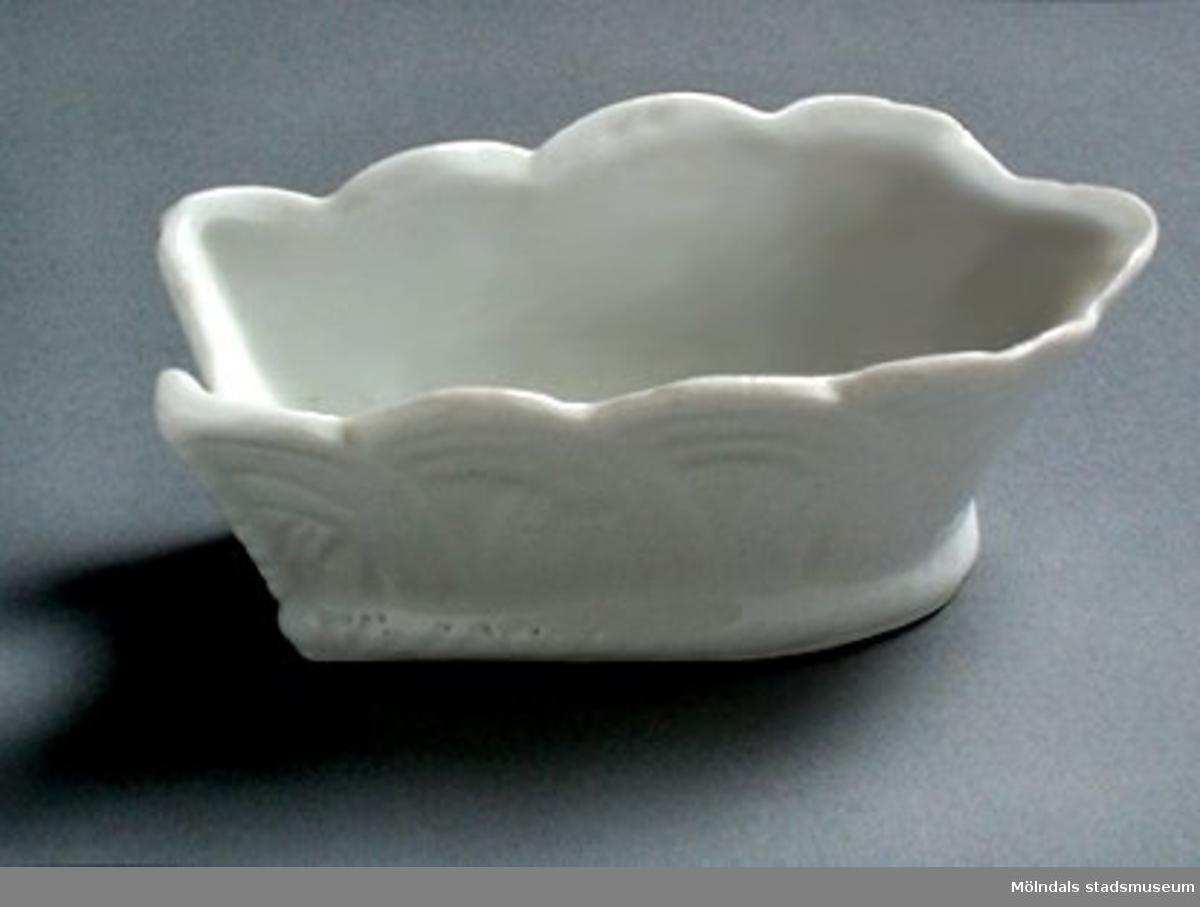 Liten avlång skål i vitt porslin. I ena kanten u-formad intagning. Korgflätningsmönster på utsidan. 1920-tal?