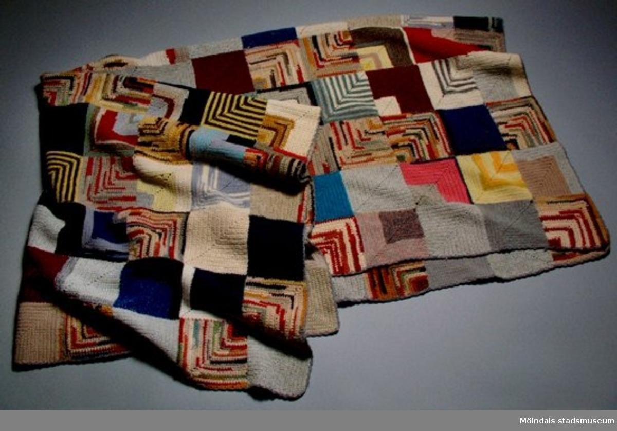 Täcke virkat av fyrkantiga rutor i restgarn och ihopsytt. Många färger.
