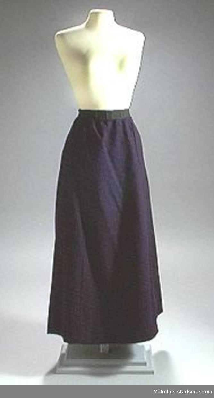 Mörkblå kjol fodrad med mörkblått bomullstyg. Hankar och hyskor i vänster sida.