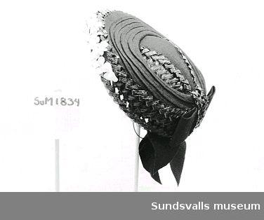 Svart hatt med bastbrätte, vita tygblommor fastsatt framtill, filtkulle och rosett baktill.