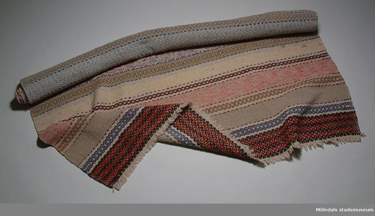 Vävd matta i olika ränder. Beige, rosa, blå och rödsvarta partier. Kort frans.