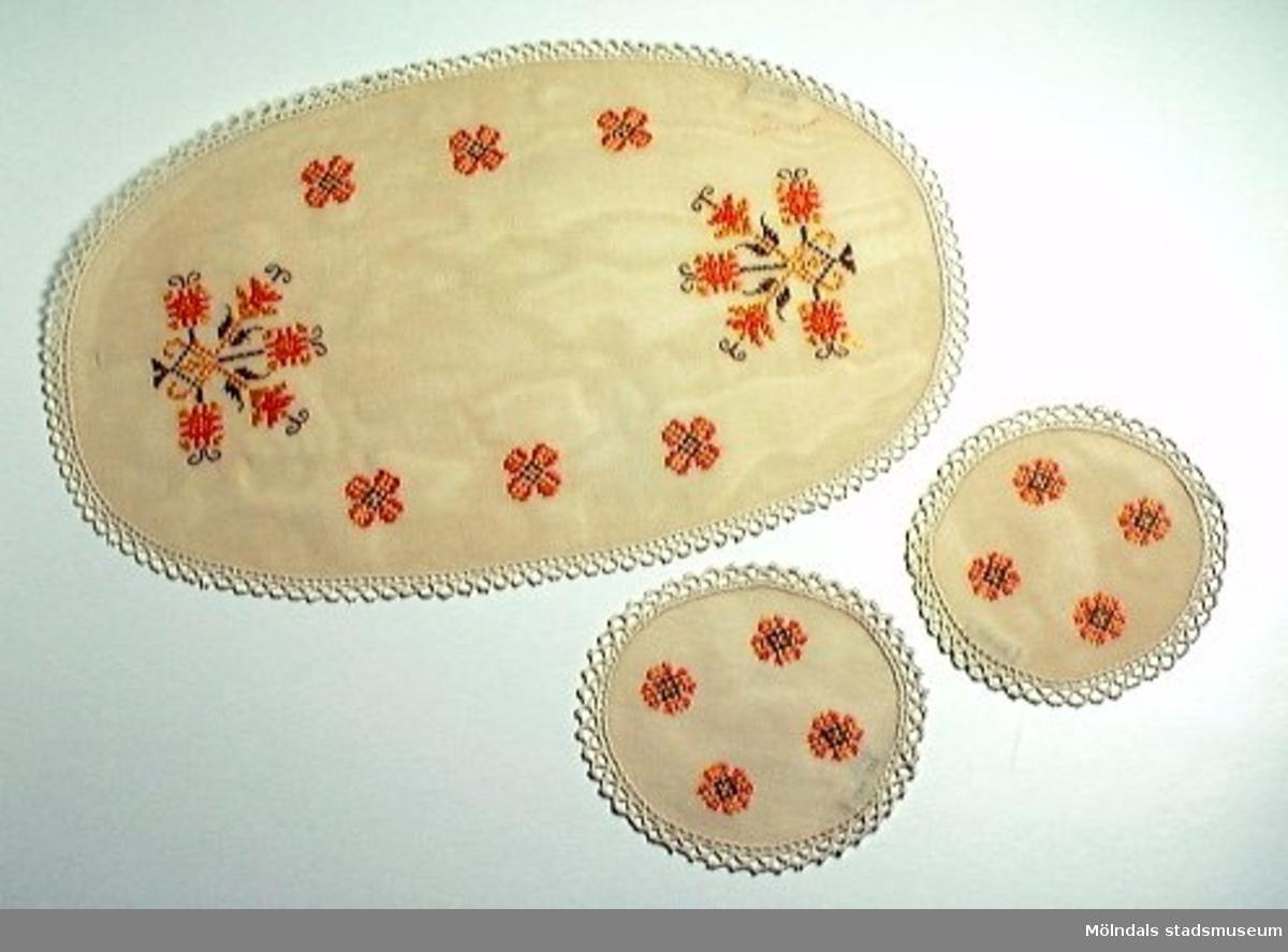 Två ovala smådukar med spetskant och fyra små broderade blommor (korsstygn) i orange, gult och brunt. Diam: 140.En oval tillhörande duk. L: 440, B: 250. Spetskant runt om, sex små blommor och två större blommönster (korsstygn) i orange, gult och brunt. Handbroderat. Tygets bottenfärg på samtliga dukar är beige.