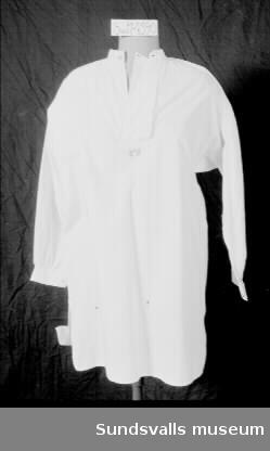 Vit bomullsskjorta. Rak modell med ståkrage och sprund i sidorna. Monogram på bröstet. Knäpps med en silverfärgad knapp i halsen.