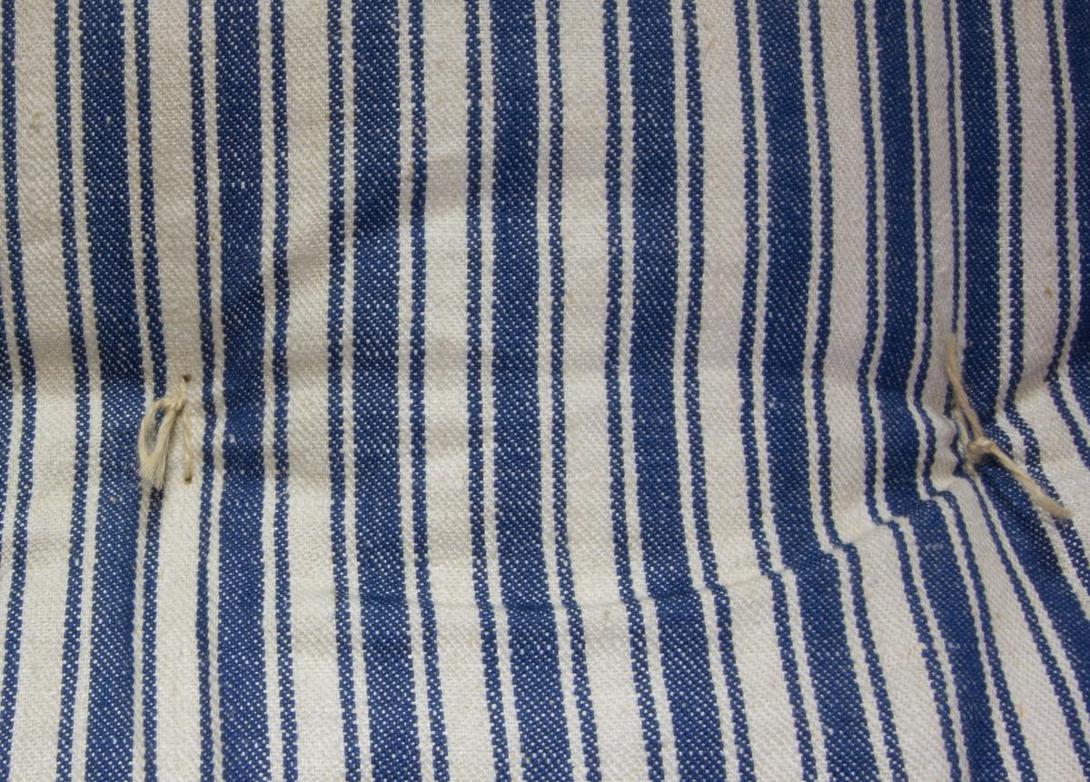 Bolster, tillverkat av linnetyg, randigt i blått och vitt, kypert med inslagseffekt. Flera längder hopsydda för att få bredden. Hand- och maskinsytt. Puskor enkelknutna av lingarn. Fyllning av halm.