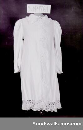 Morgonrock sydd i vitt bomullstyg med invävt stjärnmönster. Formsydd i ryggen. Nedvikt krage med virkad uddspetskant. Knäppning mitt fram med tre vita knappar. Uddspets längs knäppningen och fållen nertill. Lång rak ärm med puff vid axeln.