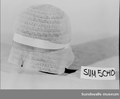 Beige, klockformad hatt med sluttande brätte. Runt kullen ligger två ripsband i beige och brunt. Fodrad med textil. Inuti hatten på en lös papperslapp står texten '120. 20-tal'.