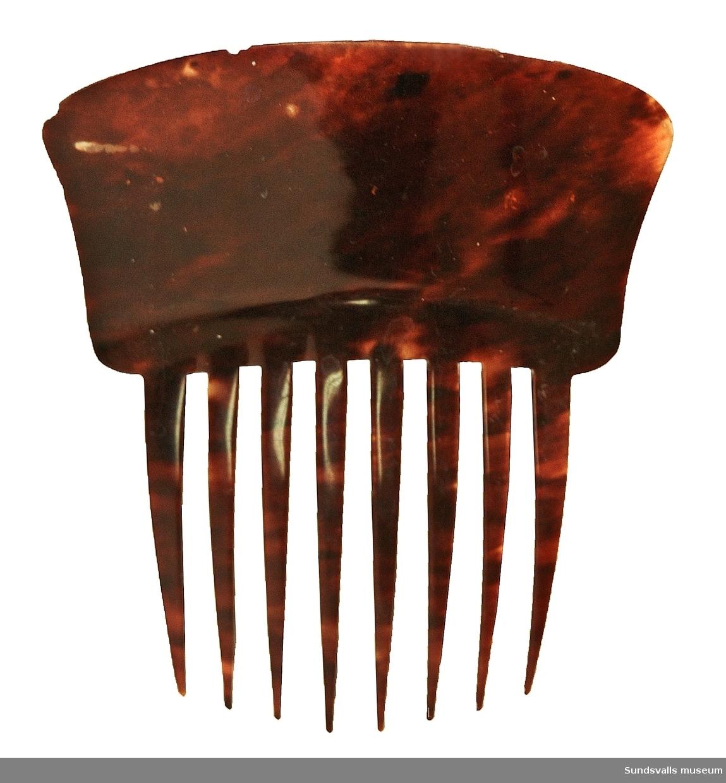 SuM 5685:1-3 tre stycken prydnadskammar i olika utförande. SuM 5685:1 är tillverkad i plast, har ett genombrutet mönster och gråmelerad färg. Längd 9 cm, bredd 9,5 cm. SuM 5685:2 i brunmelerad plast. Längd 11,5 cm, bredd 10 cm. SuM 5685:3 är dekorerad med en kulrad i gulbrunt, resten av kammen har en gulaktig färg. Material? Längd 10 cm, bredd 11 cm.