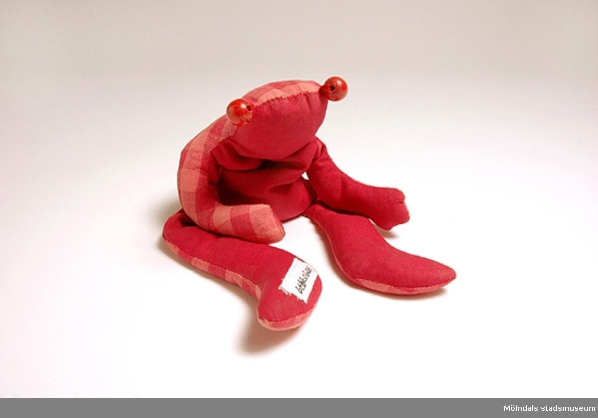 """Tyggroda fylld med risgryn - röd på den ena sidan och rödrutig på den andra sidan. Två röda träkulor som ögon.Givaren har sytt risgrodan efter modell i ett skyltfönster. Risgrodan användes som en rolig slapp """"leksak"""" - antistress. Man kunde forma den till olika roliga sitt- och liggställningar. Populär bland barn."""