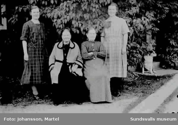 Grupporträtt i trädgården: Sigrid J. Fru Öh, Fru Persson, Märta Johansson samt en hund.