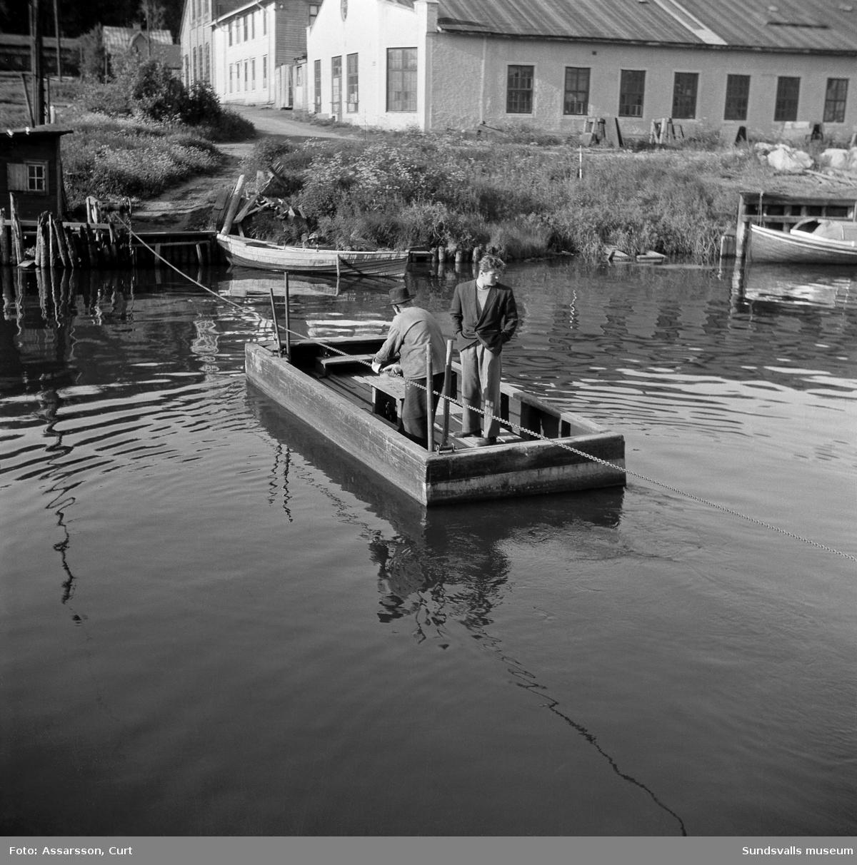 Den gamla färjan vid Sundsvalls Verkstäder. Färjan korsade Selångersån och förkortade gångvägen för dem som arbetade på Sundsvalls Verkstäder samt Laurents såg intill. Färjan drogs för hand med kedja som fick sänkas ned då båtar skulle passera. 1948 kostade överfarten 5 öre.