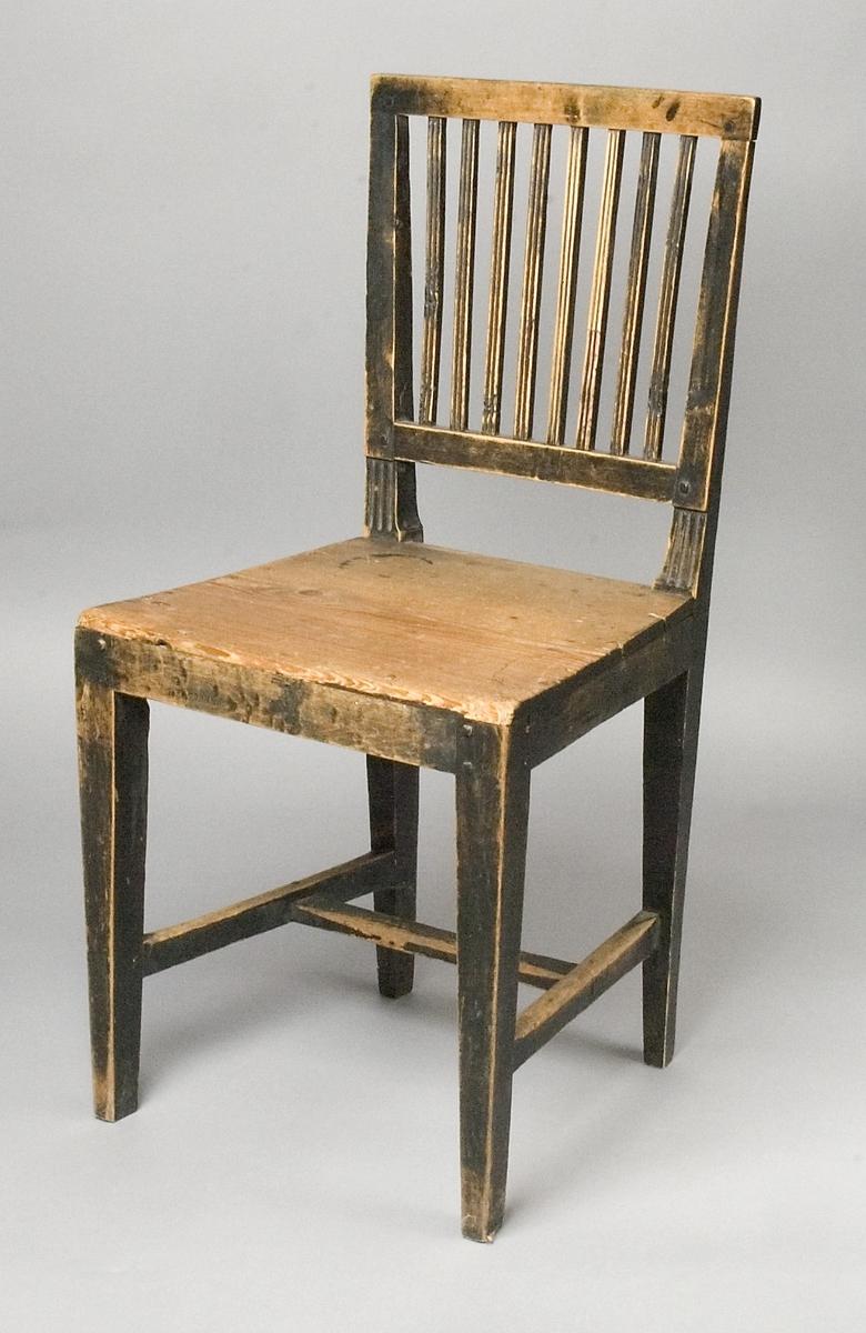 Stol tillverkad av trä. Trapetsformad rygg med spjällor. Sits av trä med rak sarg. Raka ben som avsmalnar nedåt. Benen hålls samman av ett fotkryss.