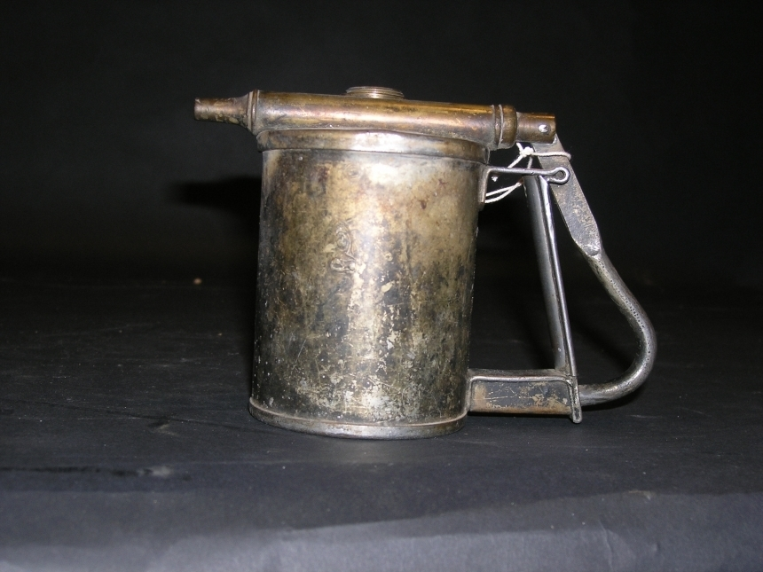 Oljekanna använd vid Postens Tryckeri. Form av en cylinder.Försedd med handtag så konstruerat att man med ett tryck pumpar utolja ur behållaren. Inskription på ovansidan: DRGM