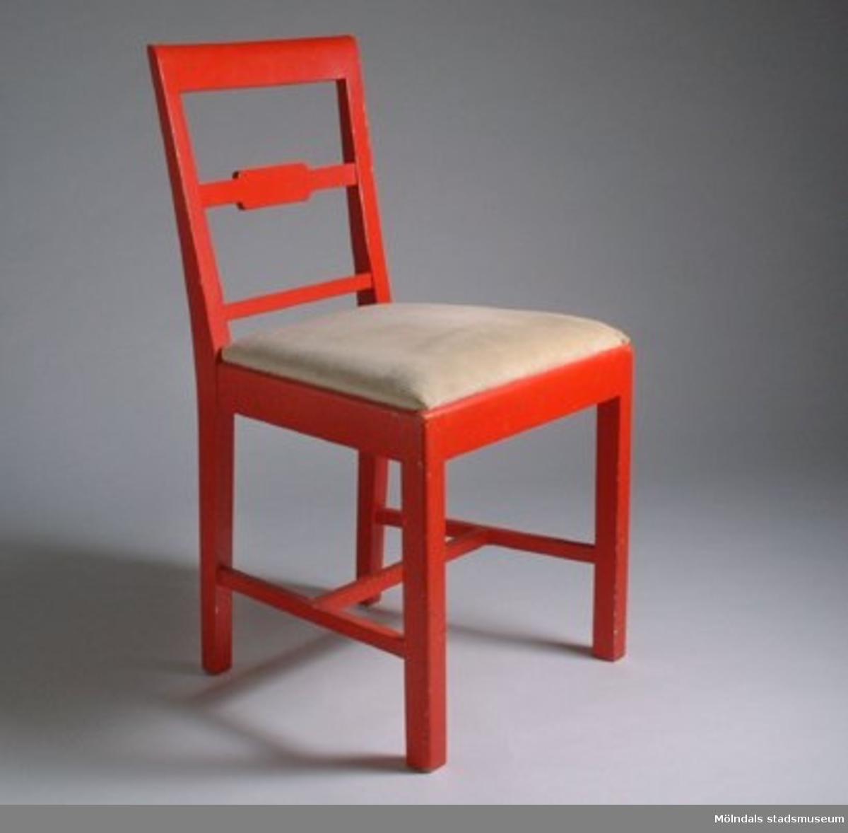Röda stolar med beige manschesterfodrad sits. Ena stolens sits är lös.Under sitsarna står med blyerts ett namn och nummer.Tillhört personalbostad på 1940-tal.F.d. inv. nr MM 03025:1-2.