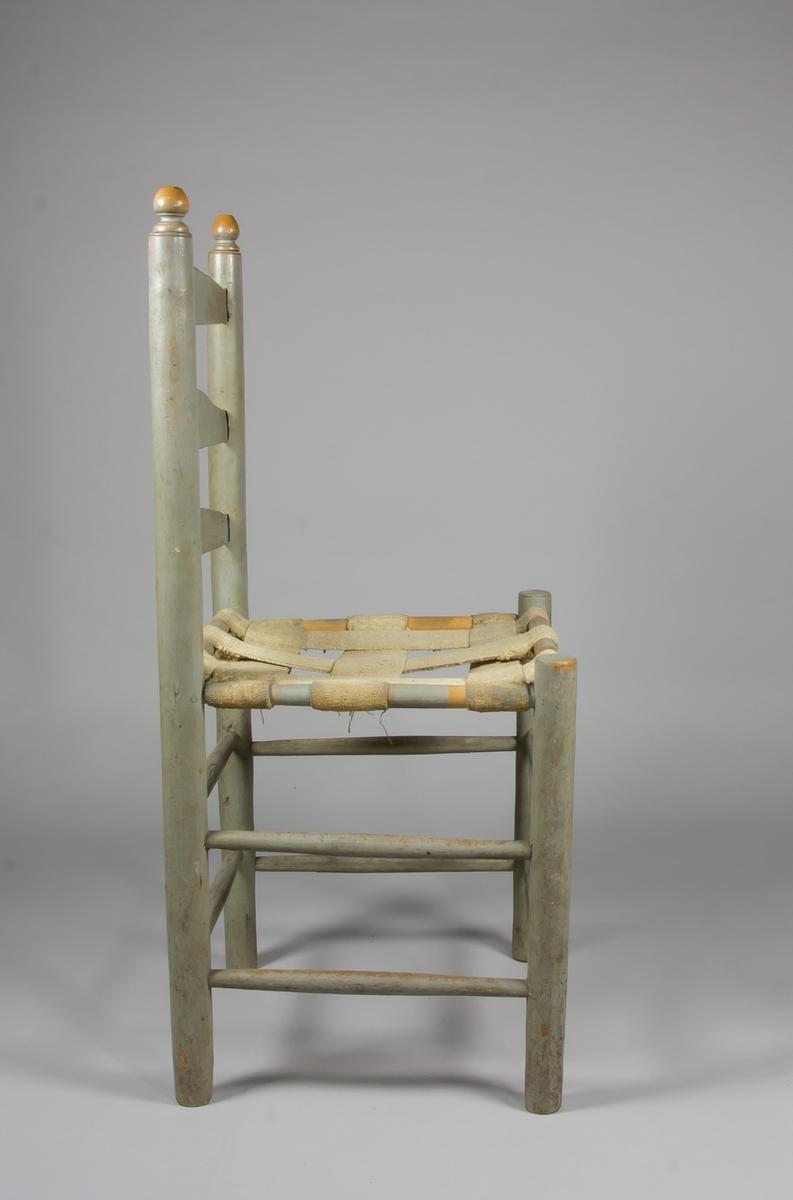 Stegstol i målat trä, sannolikt björk. Ryggstolpar med svarvade knoppar. Mellan stolparna tre slåar, sk. steg, med mjukt svängda krön. Sits av sadelgjordar. Åtta stabiliserande tvärslåar binder samman de raka benen. Dyna i vitt och brunt.