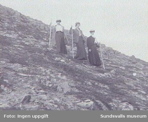 Tre kvinnor med vandringsstavar och långa kjolar, går nedför bergsluttning.