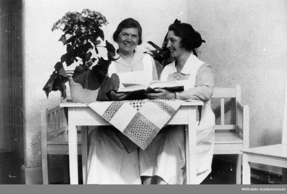 Två kvinnor sitter vid ett bord och tittar i en bok, Stretereds skolhem, cirka 1930.