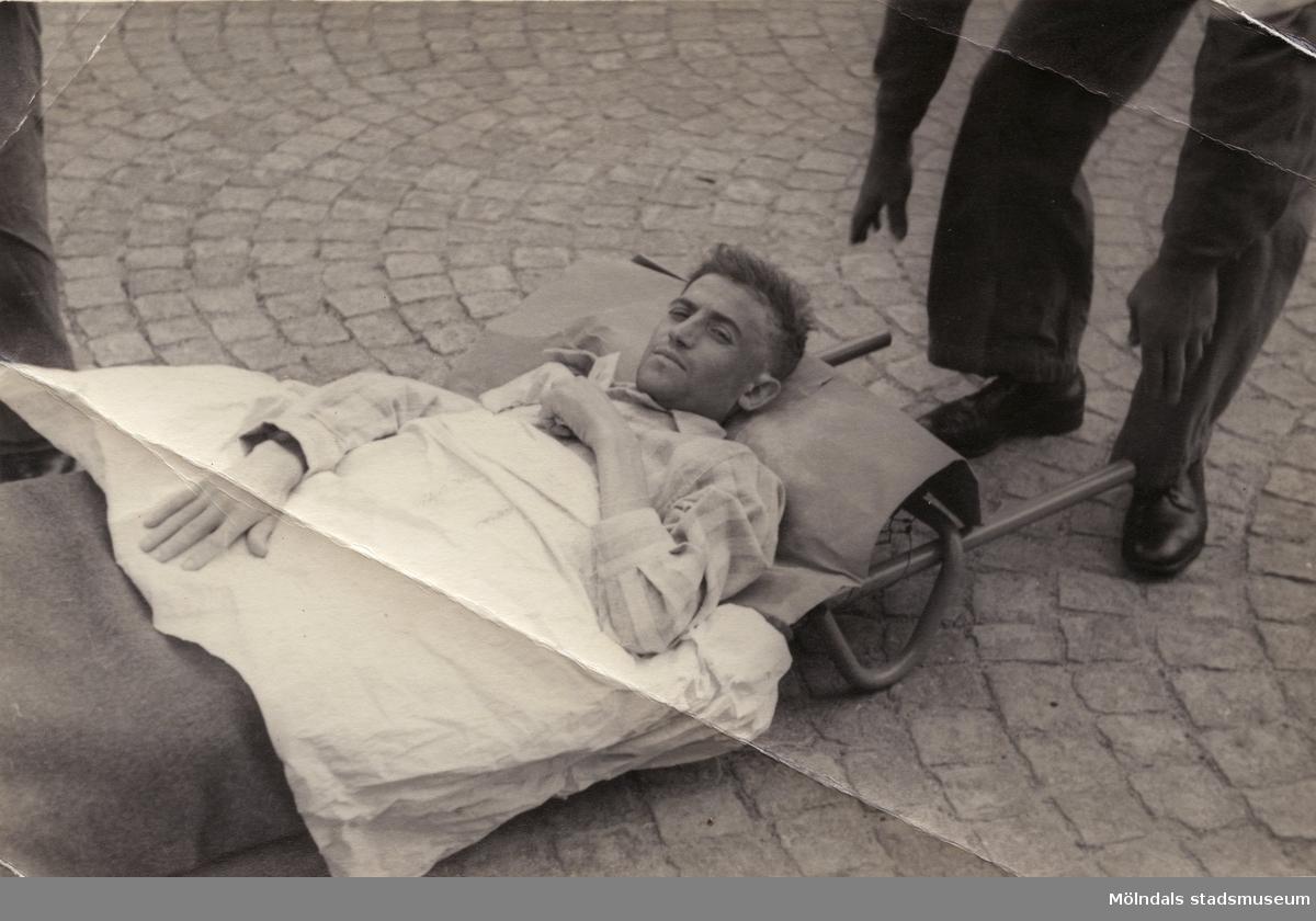 """""""Karantänsförläggning"""" på Kvarnbyskolan för flyktingar från koncentrationsläger i Tyskland 1945. Manlig flykting som bärs på bår."""