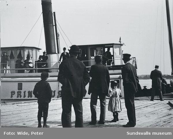 Passagerarångbåten Prins Gustaf vid kaj. Åskådare, bla a far och dotter, på kajen.