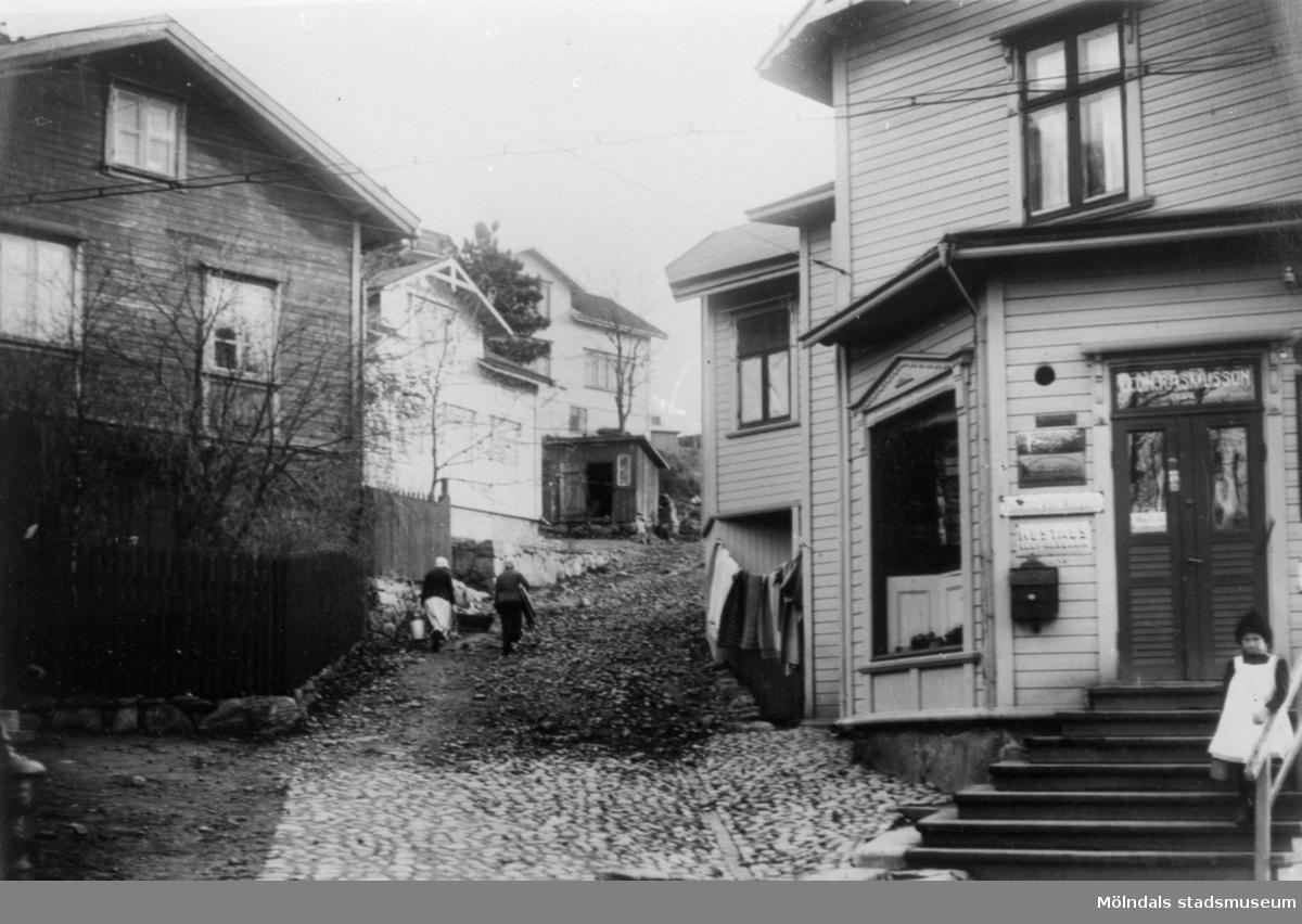 """Lundsstigens (nuvarande Millbergsstigen) mynning på Forsåkersgatan, år 1921. Till höger Leon Rasmussons filialaffär (senare """"Majkvists"""") vilken nu är riven."""